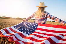 American Female Farmer In Casual Clothing With Arms Spread Open Holding USA Flag In Wheat Field.