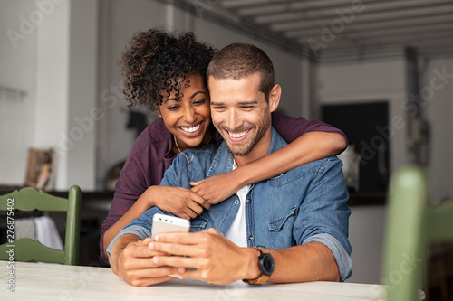 Fotografiet  Happy couple looking at phone together