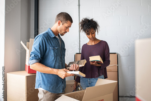 Poster de jardin Route Young couple unpacking books from cardboard boxes