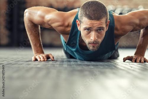 Obraz Determined man doing push ups at the gym - fototapety do salonu
