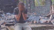 Portrait Of A Sad Man On The Background Of A Burned House, After Fire . Consequences Of Fire Disaster Accident. Ruins After Fire Disaster, Despair Concept.