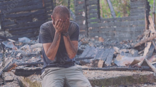 Fotomural Portrait of a sad man on the background of a burned house, after fire