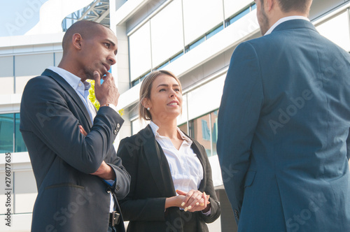 Poster Individuel Mix raced couple of company representatives meeting business partner outdoors. Man and woman in office suits talking to colleague. Business communication concept