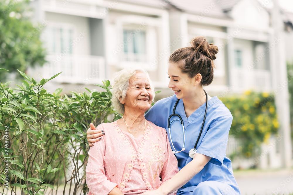 Fototapeta Caregiver with Asian elderly woman outdoor