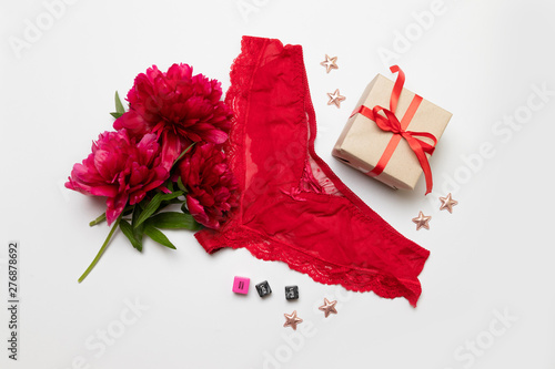 Fotografie, Obraz Romantic love relationship composition of red lingerie with a sex cubes, red branch peonies, a surprise with a gift box and a red ribbon on a grey background