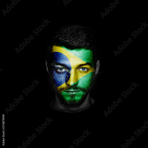 Flag of Brazil painted on a face of a man on black background. Fototapete