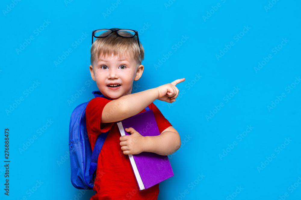 Fototapeta Back to school First grade junior lifestyle. Small boy in red t-shirt. Close up studio photo portrait of smiling boy in glasses with schoolbag and book show somethind with his finger