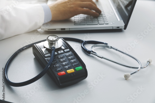 Stickers pour porte Pierre, Sable medical costs and health care expenses concept - payment terminal with stethoscope on the table in doctors office