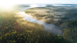 Fototapeta Na ścianę - Aerial shot of foggy autumn morning at lake. Beautiful forest and sun rays.