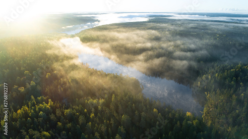 Poster Rivière de la forêt Aerial shot of foggy autumn morning at lake. Beautiful forest and sun rays.