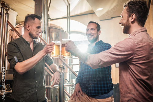 Valokuva Three men tasting fresh beer in a brewery