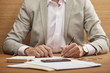 partial view of businessman in suit filling in bankruptcy form at wooden table