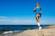 Leinwandbild Motiv Young woman running, jumping on beach