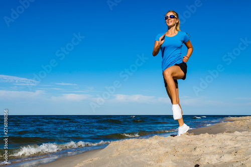 Montage in der Fensternische Logo Young woman running, jumping on beach