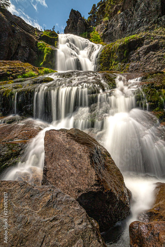 Smooth flowing waterfall cascading down rocks with vibrant green moss growing on them. Flatrock falls, Newfoundland.