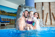 Happy Family Under The Fountain In The Swimming Pool