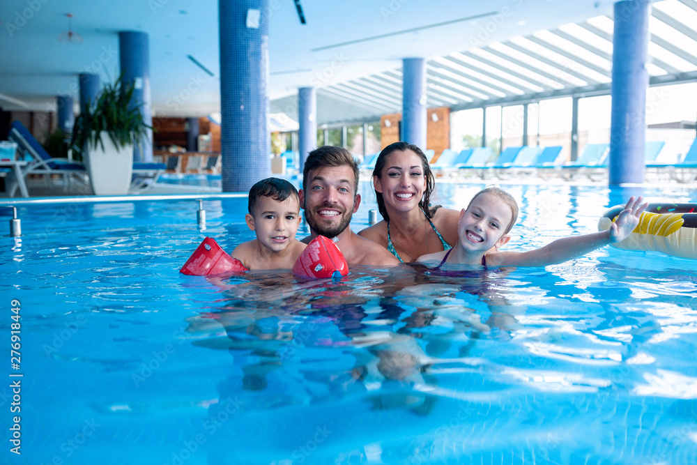 Fototapety, obrazy: Young couple having fun with their children in the water