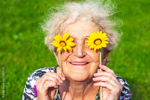 Carta da parati  A cheerful grandmother looks at the flower look of yellow daisies