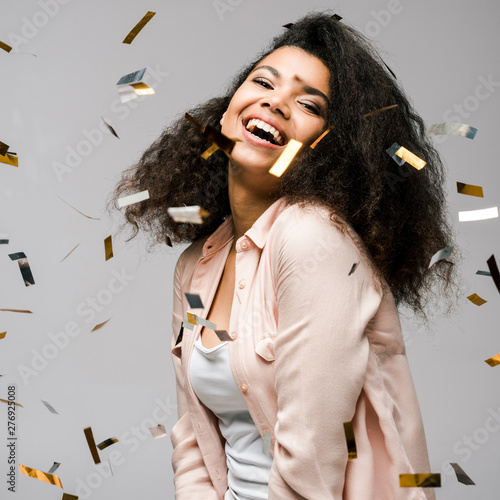 Poster Personal happy african american girl smiling near shiny confetti on grey