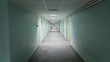 A steadicam shot of a long hallway with light green walls and stone tiled floor. The light is white and cold and there is no one around