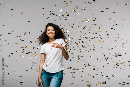 Staande foto Eigen foto young african american woman smiling near shiny confetti while standing on grey