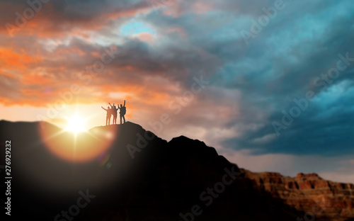 travel, tourism and people concept - group of travelers on mountain top over sunset in grand canyon national park background