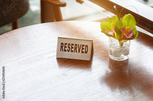 Reserved sign with flower in glass on wood table in restaurant Fototapet