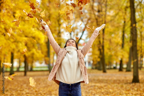 Poster Attraction parc season and people concept - happy young woman throwing maple leaves and having fun in autumn park