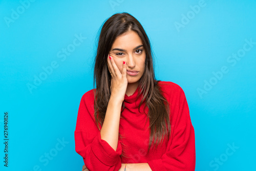 Photo Young woman with red sweater over isolated blue background unhappy and frustrate