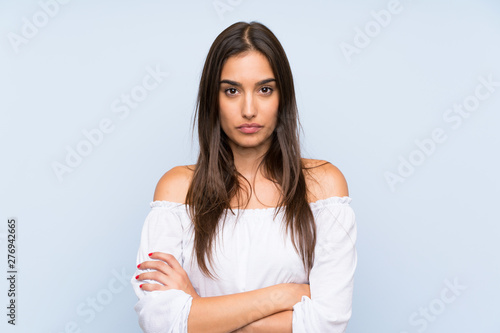 Young woman over isolated blue background keeping arms crossed Fototapeta