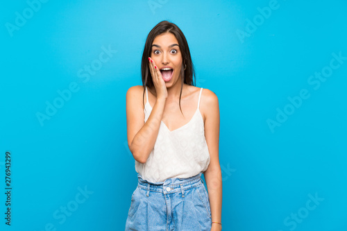 Foto Young woman over isolated blue background with surprise and shocked facial expre