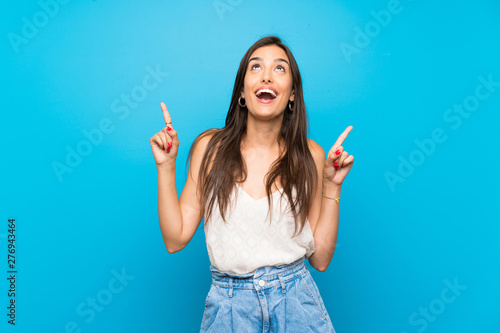 Young woman over isolated blue background surprised and pointing up Fototapet