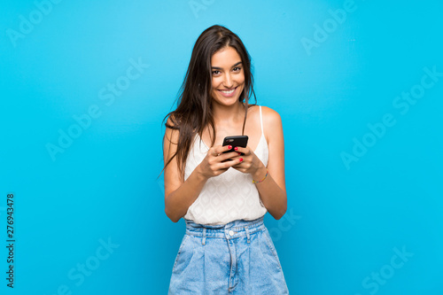 Young woman over isolated blue background sending a message with the mobile