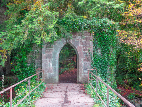 Canvas Print Overgrown archway at the end of a bridge
