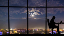The Silhouette Of Working Man Near Window On The Night City Background