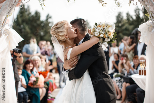 Fotografia A bride and a groom are hugging in front of the guests
