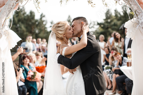 Fotografie, Tablou A bride and a groom are kissing in front of the guests.
