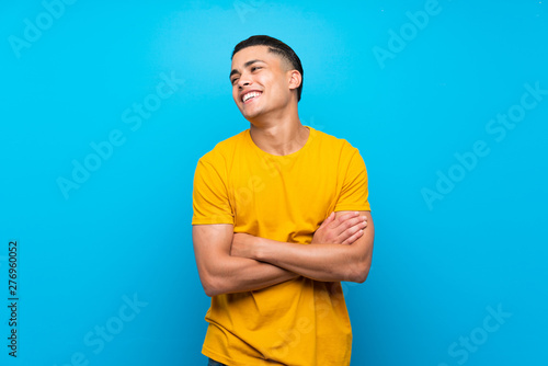 Poster Individuel Young man with yellow shirt over isolated blue background happy and smiling