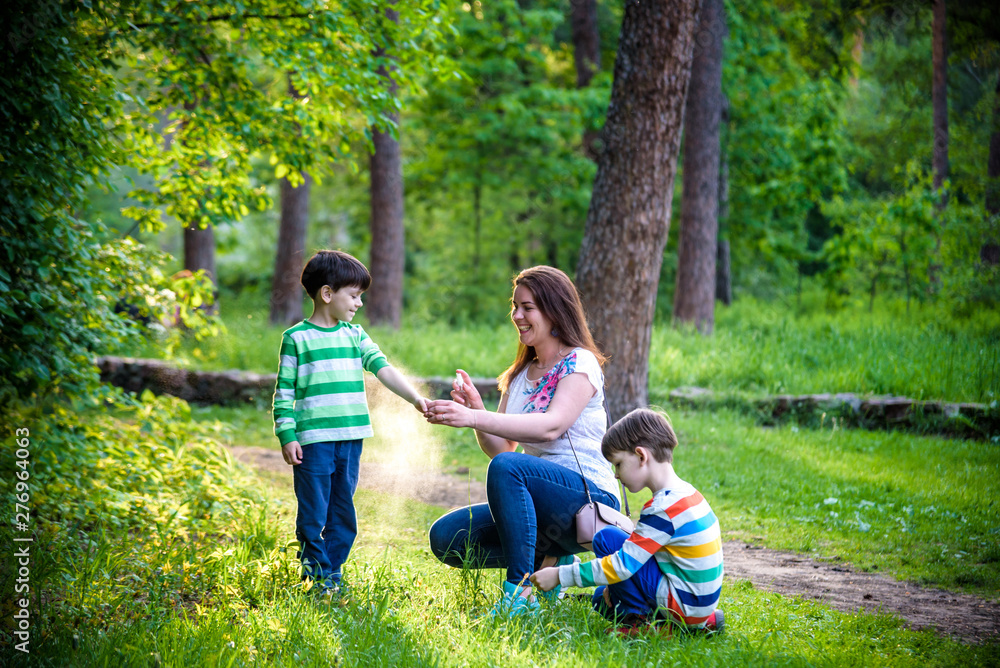 Fototapety, obrazy: Young woman mother applying insect repellent to her two son before forest hike beautiful summer day or evening. Protecting children from biting insects at summer. Active leisure with kids
