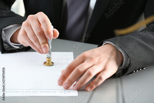 Male notary stamping document at table, closeup Canvas Print