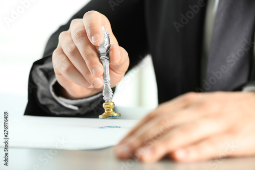 Male notary stamping document at table, closeup Wallpaper Mural
