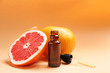 Leinwandbild Motiv Bottle of essential oil and fresh grapefruits on color background