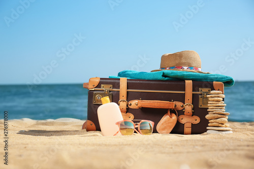Foto auf Leinwand Bekannte Orte in Asien Suitcase and beach accessories on sand near sea. Space for text