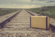 Vintage Suitcase In The Middle Of Railroad Tracks On The Prairies