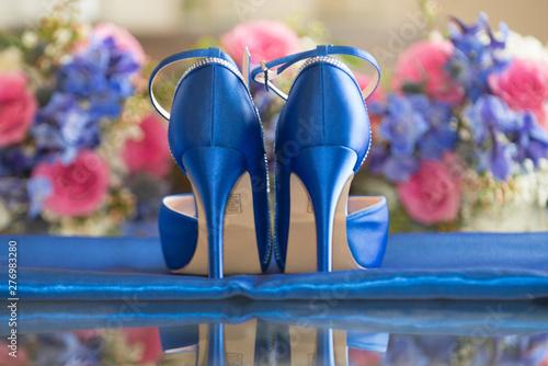 Fotografia  Blue bridal stilleto shoes on blue cloth on reflective surface with flower bouqu
