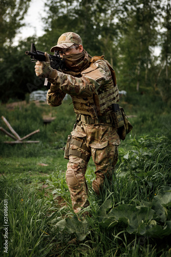 Fotografía  Airsoft soldier in full ammunition with rifle playing strikeball in outdoor in g