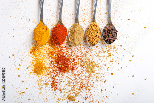 Canvas Prints Spices Various spices ( cumin, coriander, curry, paprika, chili, turmeric cinnamon, fenugreek, cardamom, basil leaf, parsley, cloves ) in spoons on white background. Top view with copy space.