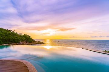 Fototapeta na wymiar Beautiful outdoor infinity swimming pool in hotel resort with sea ocean view and white cloud blue sky