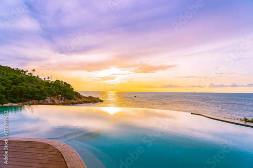 Obraz Beautiful outdoor infinity swimming pool in hotel resort with sea ocean view and white cloud blue sky - fototapety do salonu