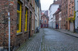 Picturesque old street of Bruges with traditional medieval houses, cobbled road and bicycle. Cityscape of Bruges streets.